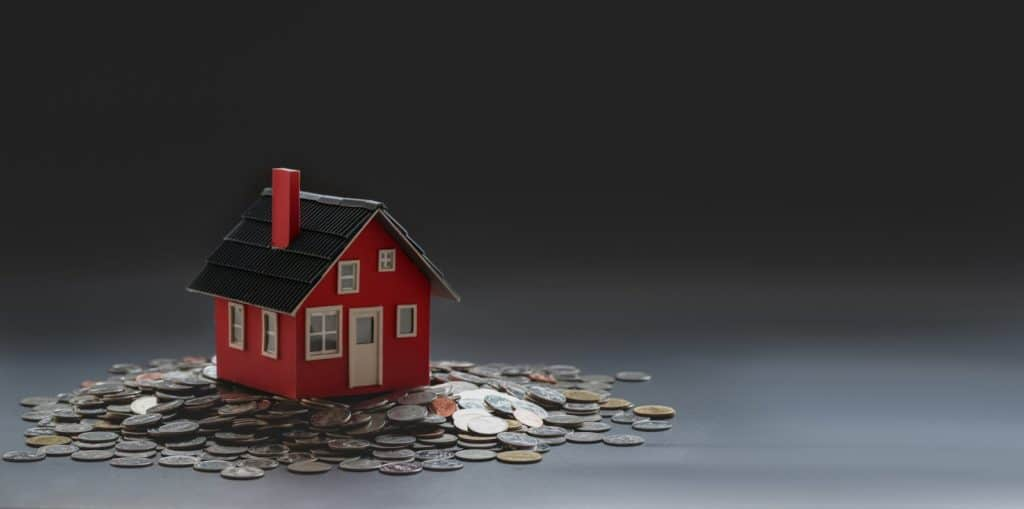 Photo of A Miniature House And Coins