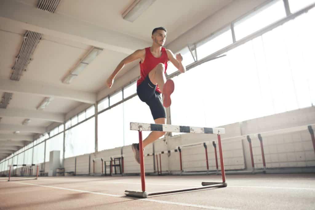 Photo of a man jumping a hurdle