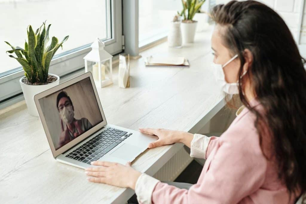 Photo of a woman on her laptop; stay safe as a virtual friend
