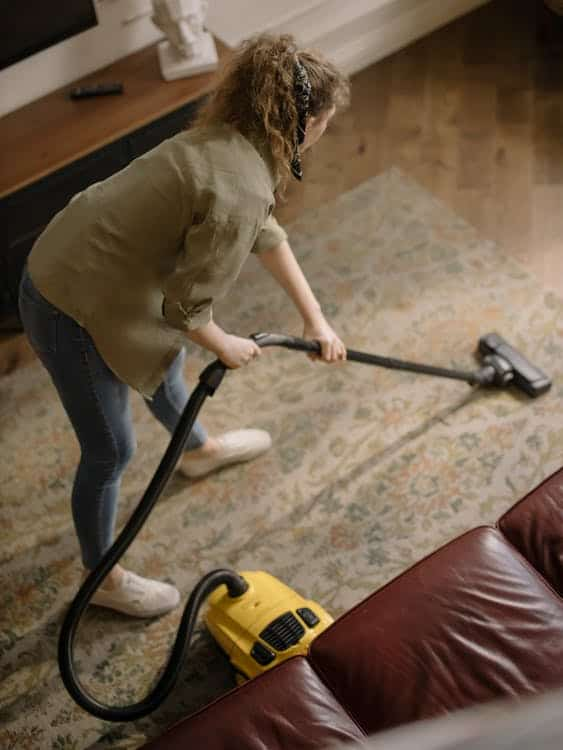 Photo of a teen cleaning the carpet; a great side hustle for teens