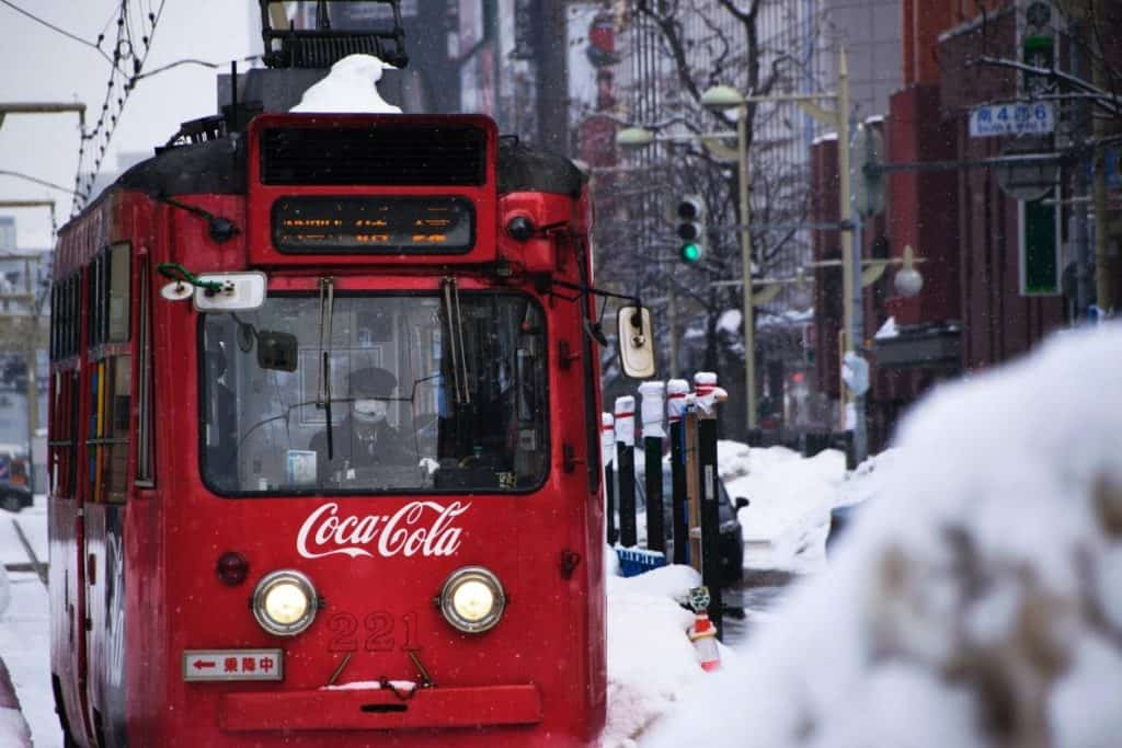 Photo of a bus painted with Cocacola; get paid to advertise companies using your car
