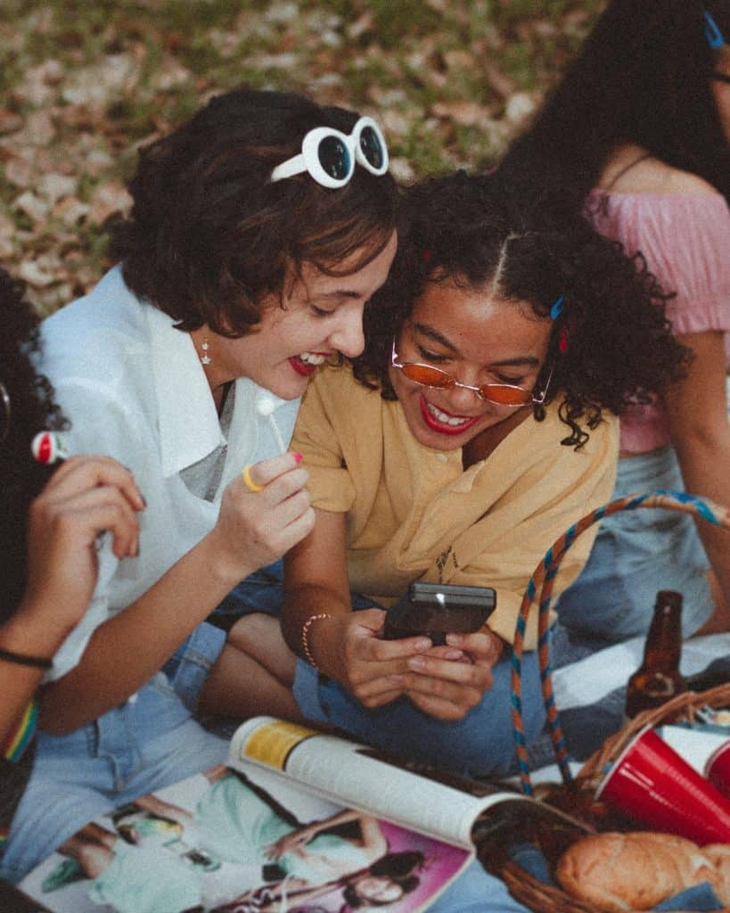 Photo of ladies laughing over a phone; you can ask family & friends for Under The Table Jobs